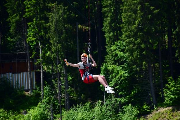 Un giovane con un casco è saltato dal bungee jumping e ora è appeso a una corda, oscillando e riprendendosi su una videocamera sportiva su uno sfondo sfocato di una foresta verde