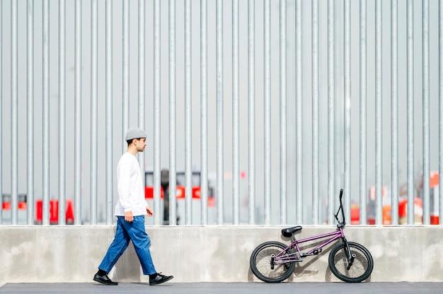 Giovane uomo accanto alla sua bicicletta in posa