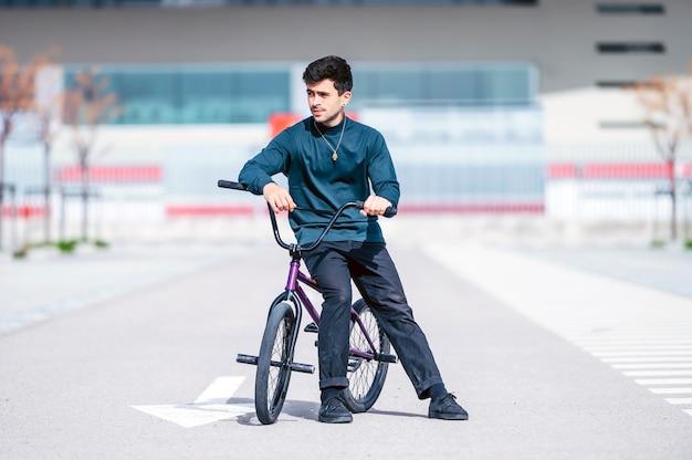 Giovane uomo accanto alla sua bicicletta