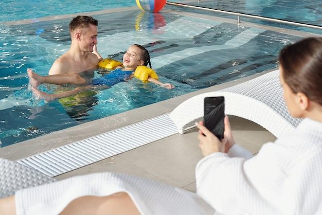 Il giovane e la sua piccola figlia ridente giocano in piscina mentre una donna bruna in accappatoio scatta foto di loro nel centro termale