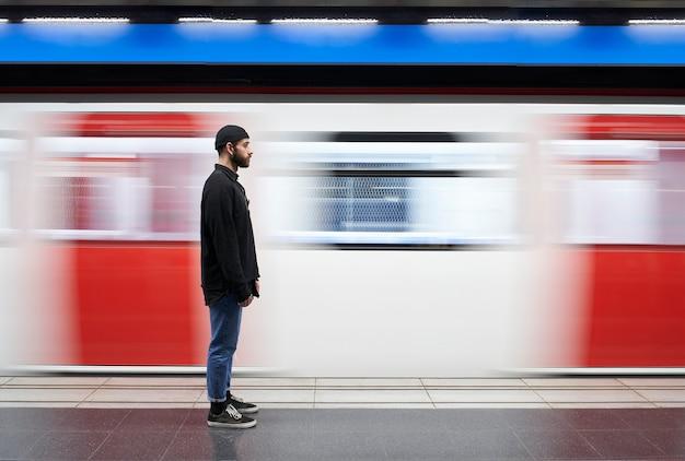 Giovane uomo dalla sua parte con una maschera sulla piattaforma della metropolitana