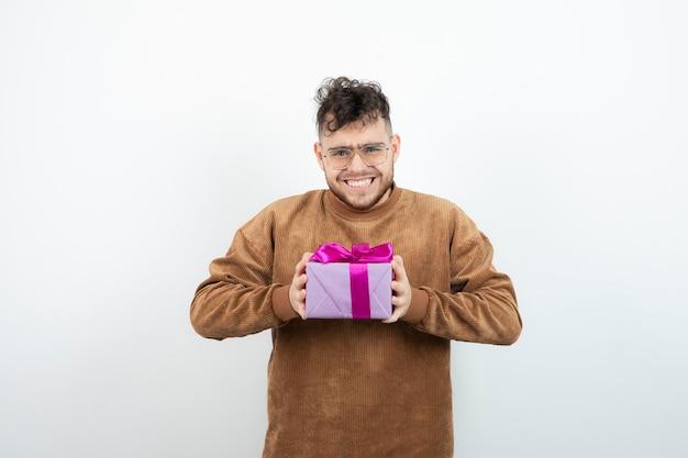 Giovane che tiene grande confezione regalo presente contro il muro bianco.