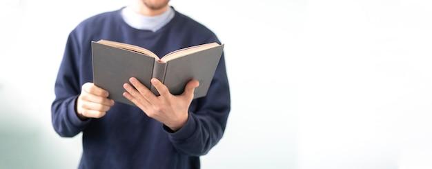 Un giovane che tiene in mano un libro, legge e acquisisce conoscenza in piedi vicino al muro, isolato