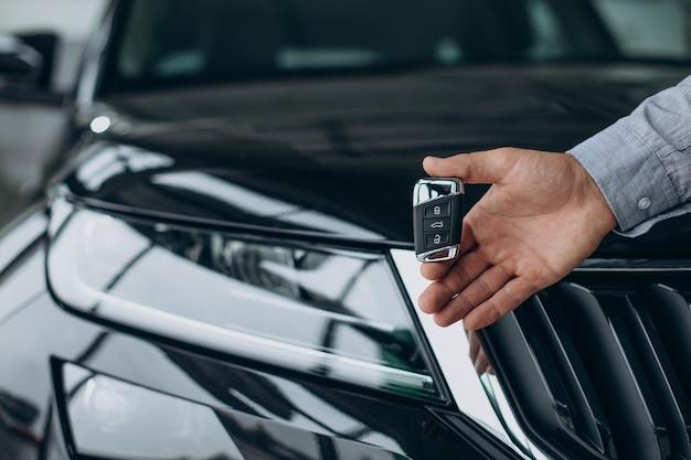 Giovane che tiene le chiavi della macchina vicino alla sua nuova auto