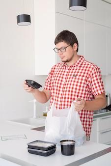 Giovane che tiene in mano un sacchetto di plastica usa e getta con consegna di cibo nella cucina moderna, annusando il cibo dalla scatola