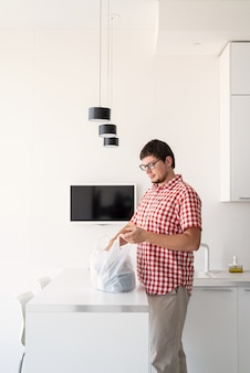 Giovane che tiene un sacchetto di plastica usa e getta con consegna di cibo nella cucina moderna