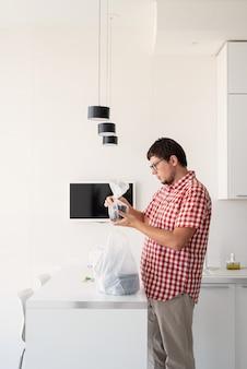 Giovane che tiene un sacchetto di plastica usa e getta con consegna di cibo nella cucina moderna Foto Premium