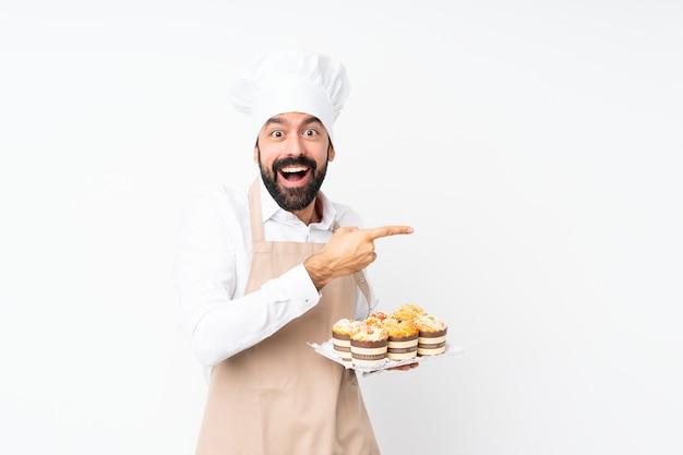 Dolce del muffin della tenuta del giovane sopra il lato sorpreso e indicante isolato