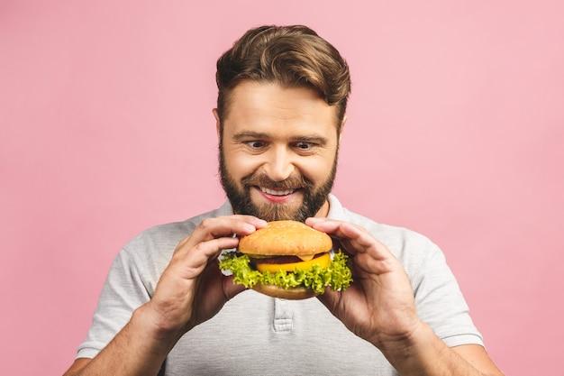 Giovane che tiene un pezzo di hamburger