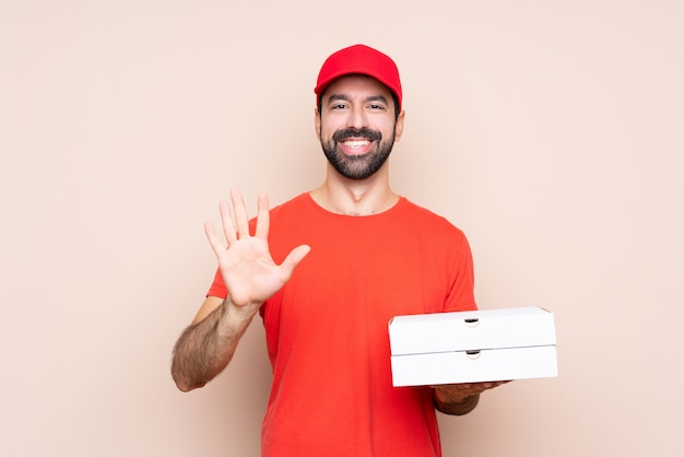 Giovane che tiene una pizza che conta cinque con le dita