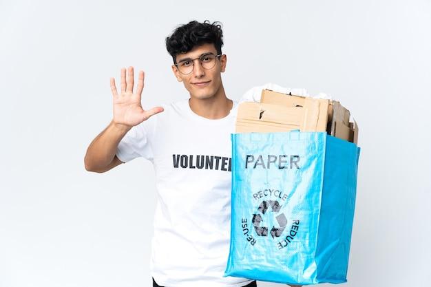 Giovane che tiene un sacchetto di riciclaggio pieno di carta che conta cinque con le dita