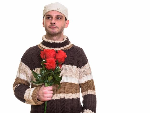 Giovane che tiene le rose rosse mentre pensa