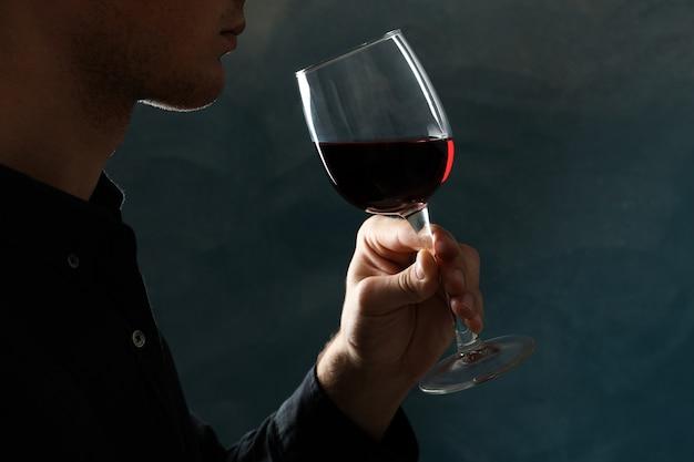 Giovane che tiene il vetro del vino rosso contro il buio