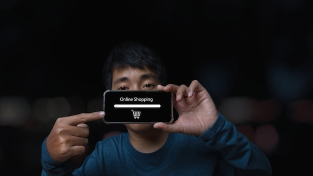 Giovane che tiene smartphone con lo shopping online. attività di commercio elettronico in linea. concetto di acquisto online.