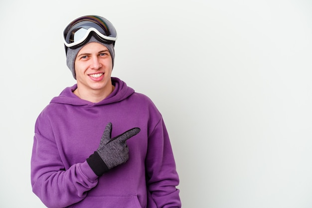 Giovane che tiene un bordo dello snowboard isolato su priorità bassa bianca che sorride e che indica da parte, mostrando qualcosa nello spazio vuoto.