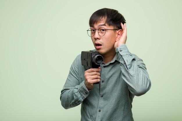 Il giovane che tiene una macchina fotografica d'annata prova ad ascoltare un gossip
