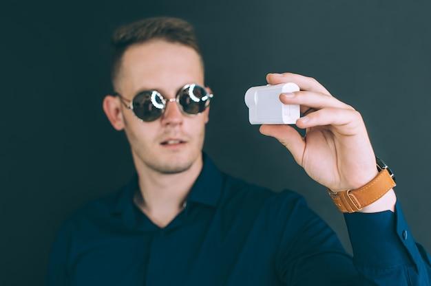 Giovane uomo, tenendo in mano camerin azione bianca, prende selfie per una videoconferenza online in studio su sfondo nero