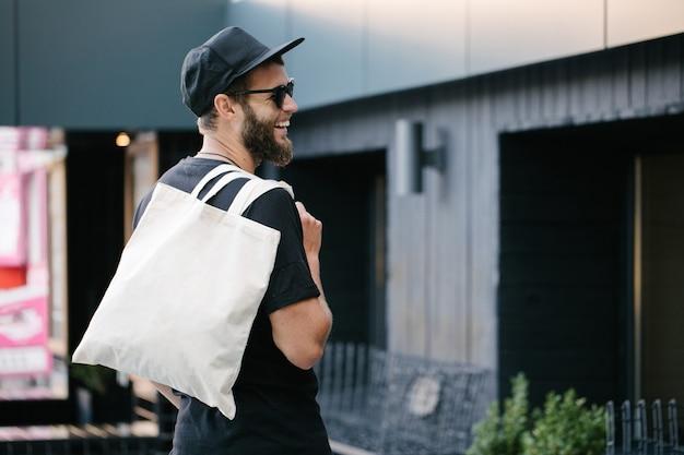 Giovane che tiene il sacchetto di eco del tessuto bianco contro il fondo urbano della città. ecologia o concetto di protezione dell'ambiente. borsa ecologica bianca per mock up.