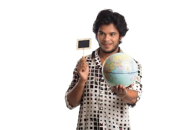 Giovane che tiene un globo del mondo e una piccola scheda su bianco