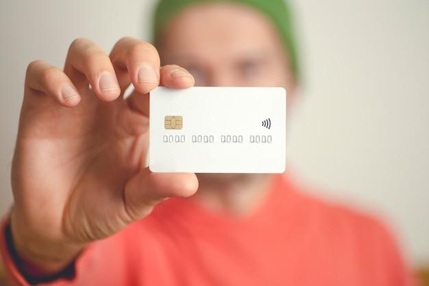Un giovane tiene una carta di credito bancaria in bianco.