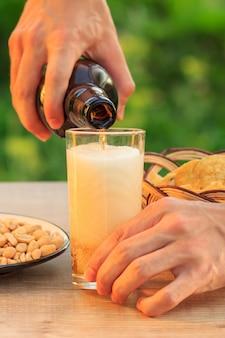Il giovane tiene una bottiglia di birra e riempie il bicchiere. mano maschio che versa birra in vetro sulla tavola di legno con le patatine fritte in canestro di vimini, arachidi in piatto e ciotola. messa a fuoco selettiva sul collo di bottiglia