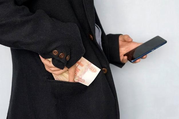 Il giovane tiene i soldi in mano e preme lo schermo dello smartphone. guadagna denaro tramite l'app mobile. affari tramite smartphone.