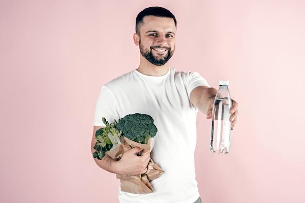 Un giovane tiene in mano un sacchetto di carta con verdure e una bottiglia d'acqua. cibo sano, vegetariano.