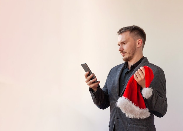 Un giovane tiene in mano un telefono e un cappello da babbo natale