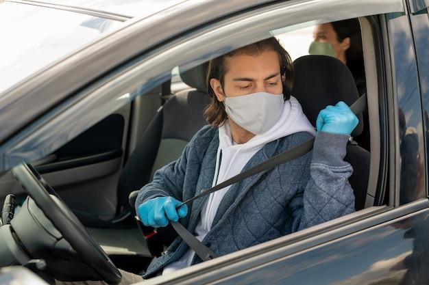 Giovane uomo in felpa con cappuccio, giacca, guanti protettivi e maschera andando a mettere la cintura di sicurezza