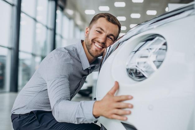 Giovane che abbraccia la sua nuova auto in un salone di auto