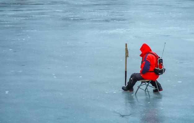 Un giovane sta pescando da un buco nel ghiaccio. pesca invernale