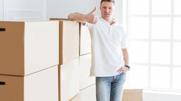 Il giovane è felice della consegna delle cose nel suo nuovo appartamento. foto con copia-spazio