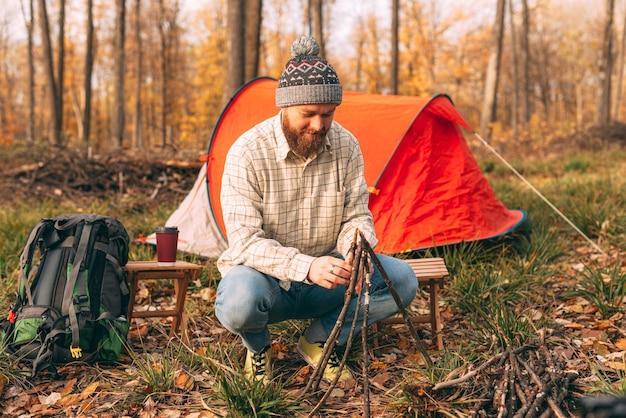 Il giovane sta facendo un falò, all'aperto nei boschi in autunno, di giorno.