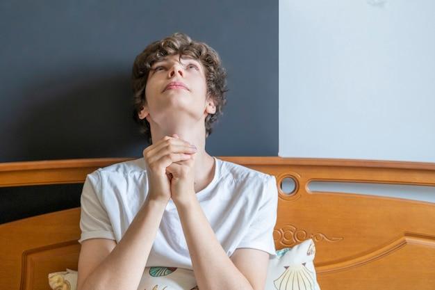 Il giovane sta pregando a letto a casa contro la finestra b
