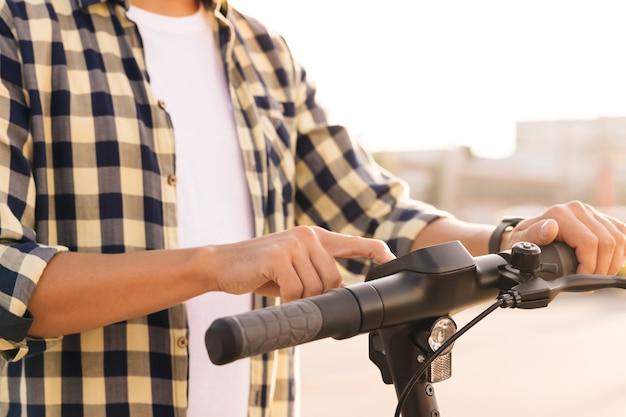 Il giovane sta spingendo il pulsante di avvio del gadget moderno e sta guidando lungo la strada della città. mani maschii del primo piano sulla ruota del motorino elettrico. concetto di trasporto alternativo ecologico