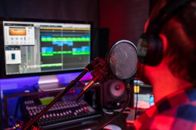 Il giovane sta cantando e registrando una nuova traccia nel posto di lavoro dello studio stereo usando il mixer e il microfono della canzone