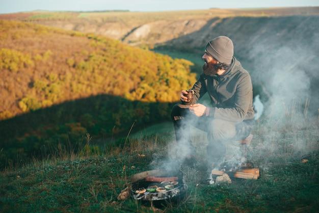 Giovane è seduto su una collina vicino a grill con una tazza di caffè in mano guardando la vista dal suo lato destro