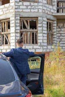 Il giovane è in piedi vicino all'auto di fronte a una casa incompiuta, un concetto di costruzione o una crisi dei mutui, incapacità di pagare per l'alloggio