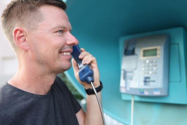 Il giovane sta parlando al telefono al concetto del dispatcher di chiamata della cabina telefonica