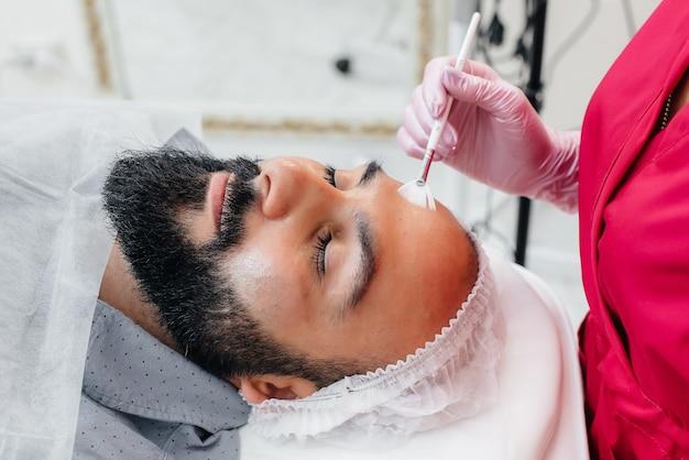 Un giovane sta subendo una procedura di peeling facciale cosmetico. cosmetologia e ringiovanimento.