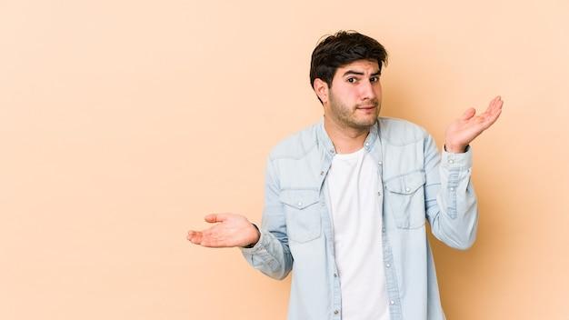 Giovane uomo isolato su sfondo beige confuso e dubbioso scrollare le spalle per tenere uno spazio di copia.