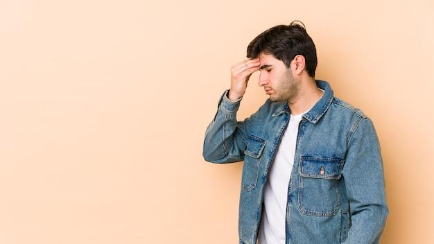 Giovane uomo isolato sul muro beige con mal di testa, toccando la parte anteriore del viso.
