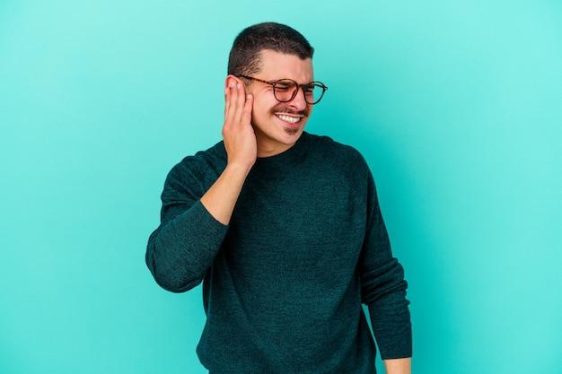 Giovane uomo isolato sul muro blu che copre le orecchie con le mani