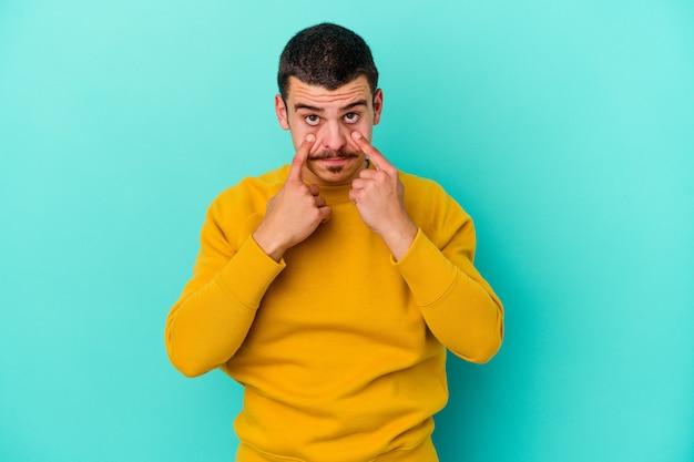 Giovane uomo isolato sul muro blu piangendo, insoddisfatto di qualcosa, agonia e concetto di confusione