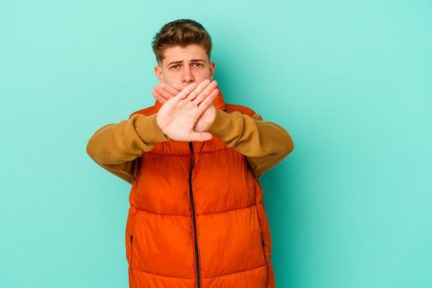 Giovane uomo isolato sulla parete blu facendo un gesto di diniego