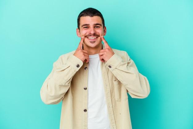 Giovane uomo isolato sulla parete blu dubitando tra due opzioni