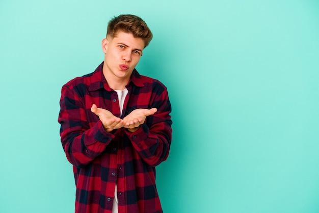 Giovane uomo isolato sul muro blu piegando le labbra e tenendo le palme per inviare un bacio d'aria