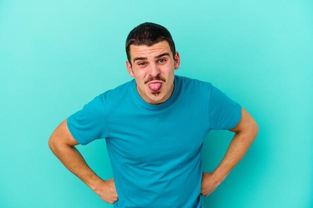 Giovane uomo isolato sulla parete blu divertente e amichevole che attacca fuori la lingua
