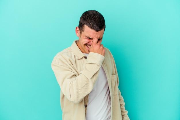 Giovane uomo isolato sulla parete blu con mal di testa, toccando la parte anteriore del viso