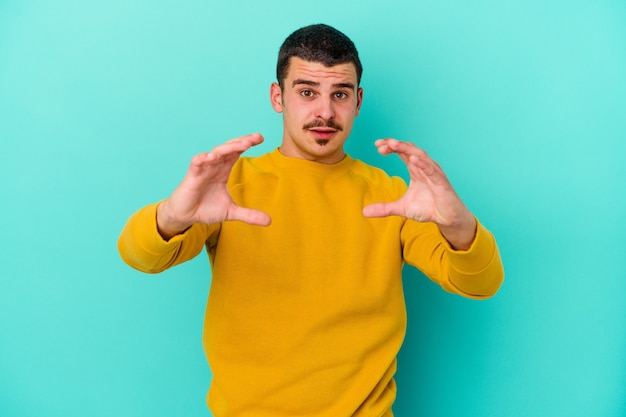 Giovane uomo isolato sulla parete blu che tiene qualcosa con le palme, offrendo alla parte anteriore